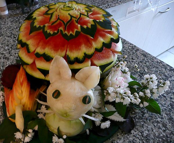 Katze aus Kohlrabi mit Melone im Hintergrund